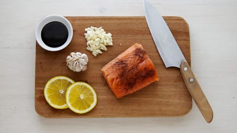 лосось на доске рядом лежит нож лимон чеснок и соевый соус
