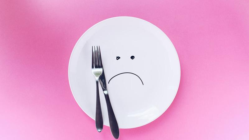 тарелка с грустным смайлом вилкой и ножом